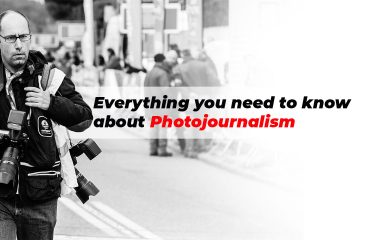 A photographer walking on the street with two DSLR where there is a writing saying everything you need to know about photojournalism