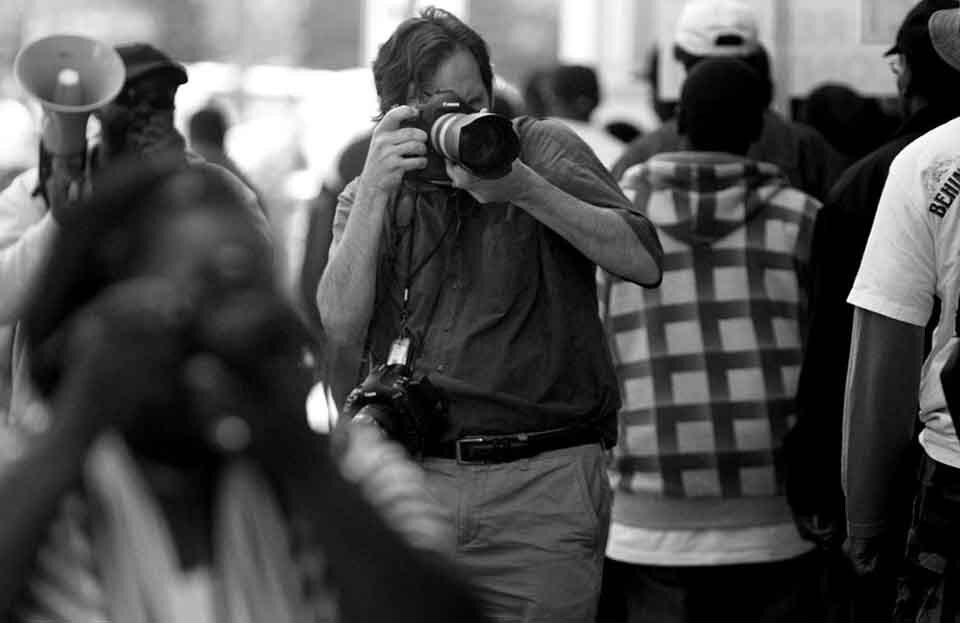 from the crowd a photojournalist taking pictures by his DSLR to show everything you need to know about photojournalism