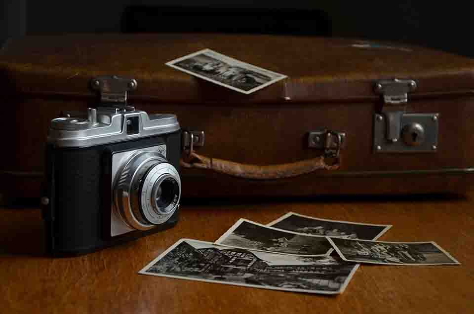 a camera and some photos are on the table