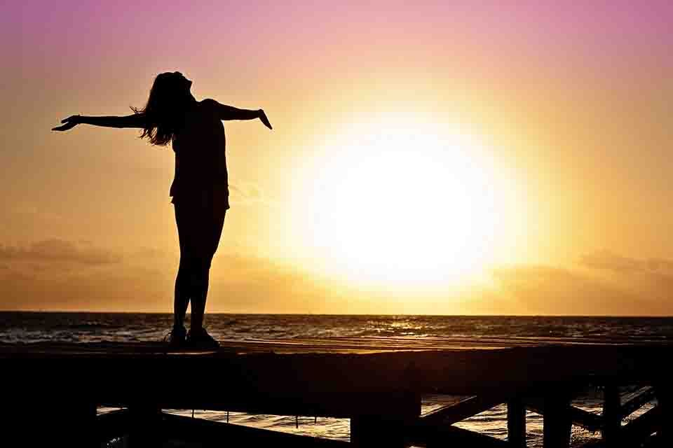 a woman standing opposite of the sun on a seaside