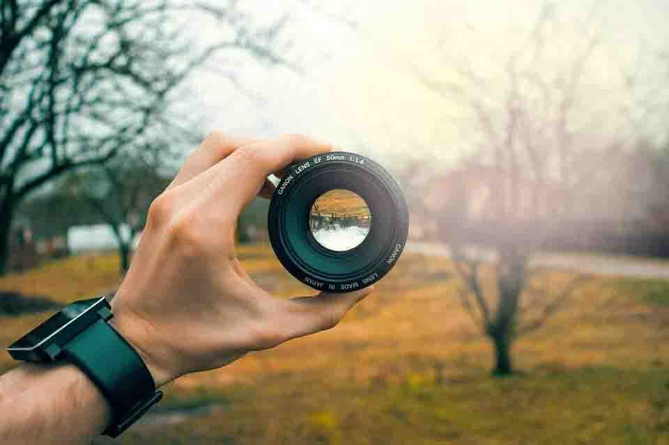 a person is holding a lense on his hand on a nature view