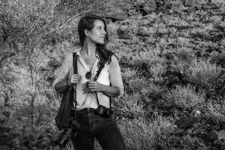 a picture of photojournalist having two camera with her in a war zone